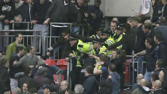 Confronto entre torcedores e guardas no jogo entre Millwall x Wigan, Copa da Inglaterra, 2013